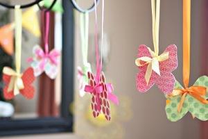 Enfeite delicado que pode ficar em cima da mesa do bolo pequenas borboletas de papel colorido presos com fitas - você prende as fitas no teto