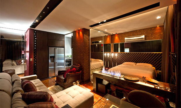 uma bancada com lareira a gas para separar a sala do quarto e, assim, aumentar e iluminar os ambientes